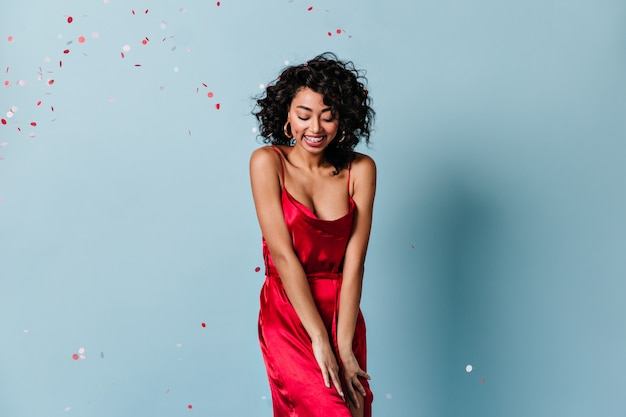 Femme frisée timide debout sous des confettis