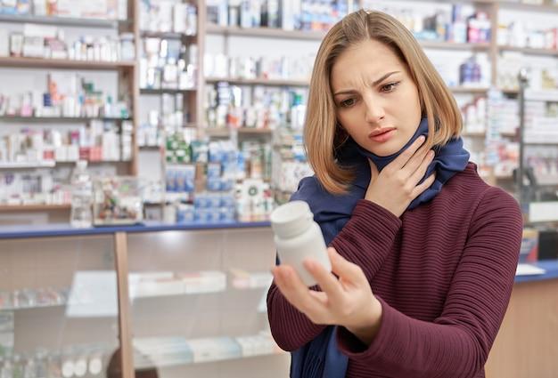 Femme fronçant les sourcils et tenant une bouteille simulée en pharmacie.