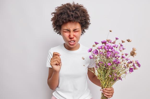 Femme fronce les sourcils le visage garde les yeux fermés réagit sur la gâchette souffre d'allergie au pollen détient des fleurs sauvages