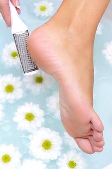 La femme frotte et nettoie le pied bien entretenu dans l'eau au moyen d'une brosse en acier de compensation