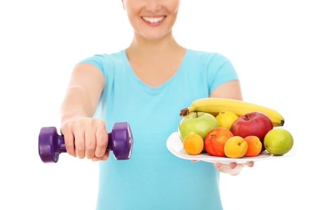 Une femme avec des fruits et des haltères