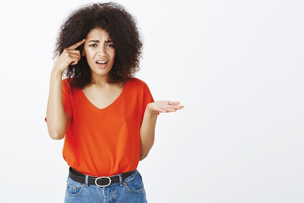 Femme frustrée avec une coiffure afro qui pose en studio