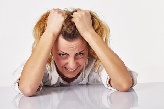 Une femme frustrée et en colère hurle et se tire les cheveux.