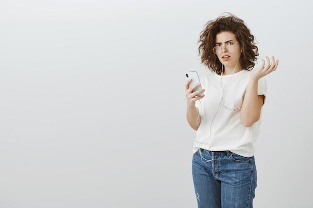 Une femme frustrée et confuse réagit à un message étrange sur un téléphone portable