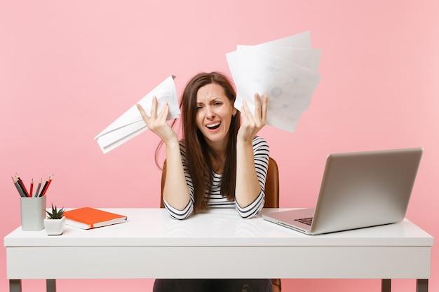 Une femme frustrée en désespoir de cause pleure en répandant des documents papier sur la main qui travaille sur le projet alors qu'elle est assise au bureau avec un ordinateur portable isolé sur fond rose. concept de carrière d'entreprise de réalisation. espace de copie.