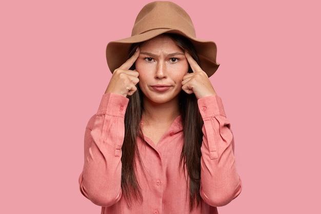 Femme frustrée avec une expression faciale mécontente, a une mauvaise mémoire, garde les deux index sur les tempes, essaie de se concentrer