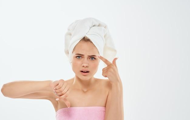 Femme frustrée faisant des gestes avec les mains et une serviette sur la tête, les épaules nues.