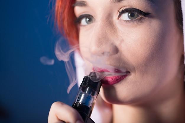 Femme fumant une cigarette électronique et exhalant de la fumée en gros plan