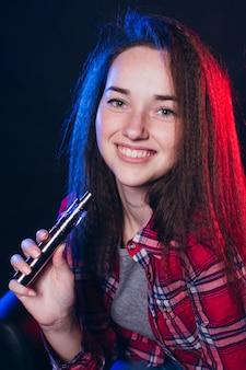 Femme fumant une cigarette électronique avec de la fumée