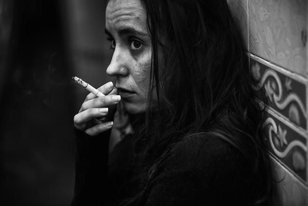 Femme fumant la cigarette seule en niveaux de gris