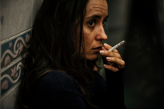 Femme fumant une cigarette seule
