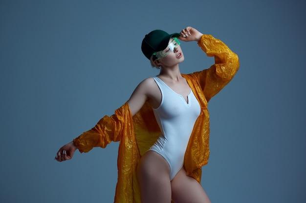 Femme futuriste sexuelle en imperméable, casquette et lunettes modernes, fond gris. femme sexy dans un style de réalité virtuelle, technologie future, concept de futurisme