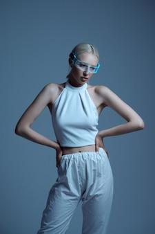 Femme futuriste sexuelle en vêtements blancs et lunettes modernes, fond gris. femme sexy dans un style de réalité virtuelle, technologie future, futurisme