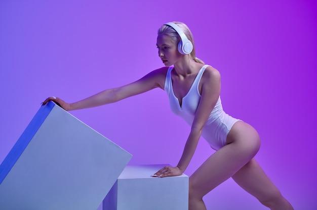 Femme futuriste sportive dans des écouteurs modernes