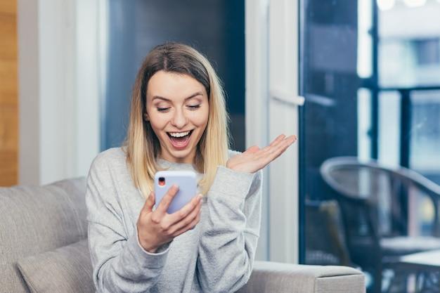 Femme gagnante criant oui se réjouissant du succès en regardant un téléphone portable