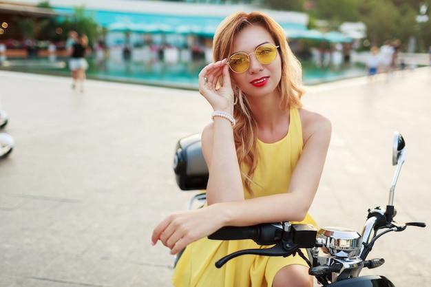 Femme gaie au gingembre à lunettes jaunes et robe vintage assis sur une moto élégante. humeur de vacances. journée d'été ensoleillée. lèvres rouges.