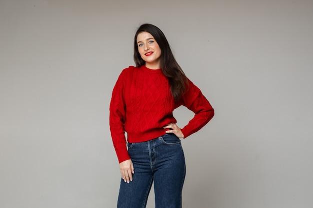 Femme gaie dans le chandail rouge chaud et les jeans bleus