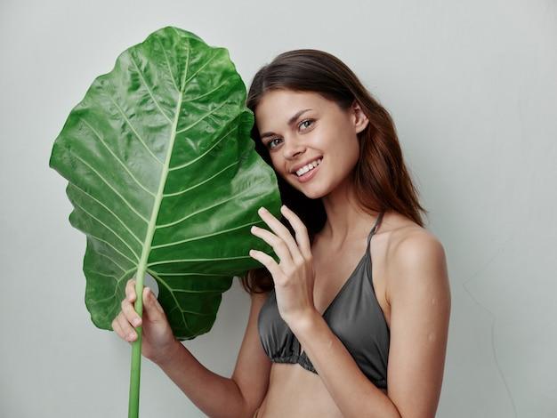 Femme gaie dans une feuille verte de maillot de bain dans le fond clair exotique de mains