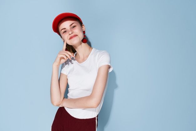 Femme gaie dans le fond bleu de mode de vie de mode d'été de casquette rouge