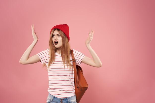 Femme gaie dans le fond rose de mode de lunettes de soleil de chapeau rouge