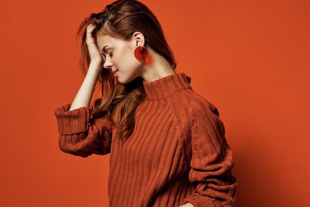 Femme gaie dans le modèle de cosmétiques de charme de boucles d'oreilles de chandail rouge