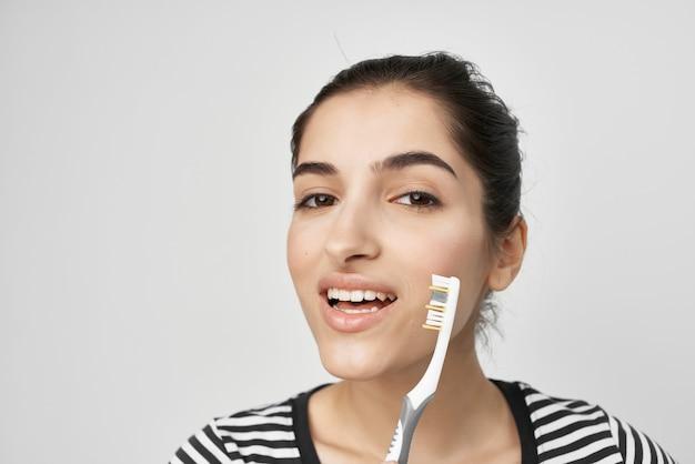Femme gaie hygiène dents nettoyage soins santé fond clair. photo de haute qualité