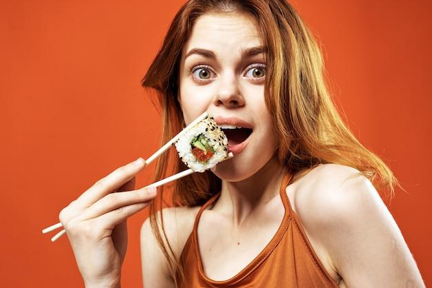 Femme gaie mangeant le fond rouge de nourriture asiatique de sushi
