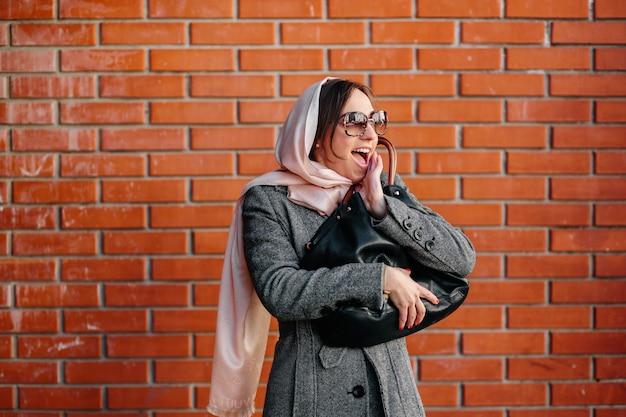 Femme gaie avec mur de briques de fond