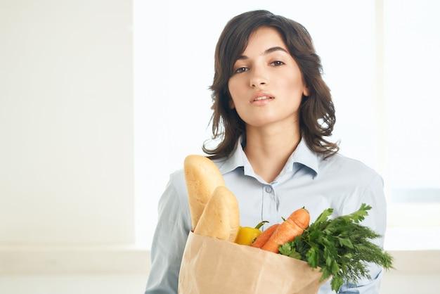 Femme gaie avec un paquet d'épicerie saine ménagère de légumes