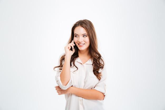 Femme gaie parlant au téléphone portable d'isolement sur un mur blanc