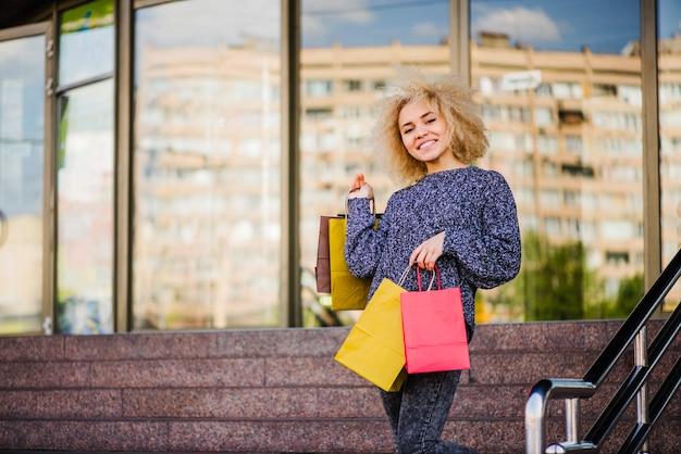 Une femme gaie qui tient des achats dans des packs vifs