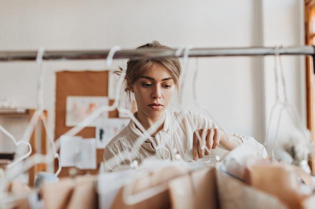 Une femme gaie regarde ses échantillons de vêtements