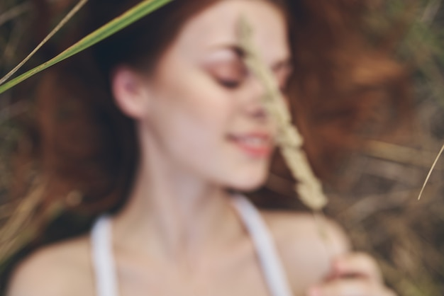 La femme gaie se trouve sur une paille dans un plan rapproché de nature de champ