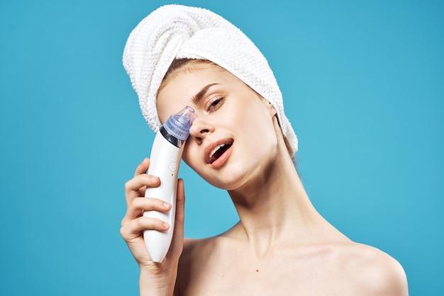 Femme gaie avec une serviette sur ses masseurs de tête dans la peau propre de dermatologie de mains