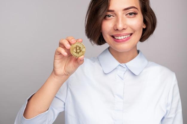 Femme gaie souriante et montrant le bitcoin
