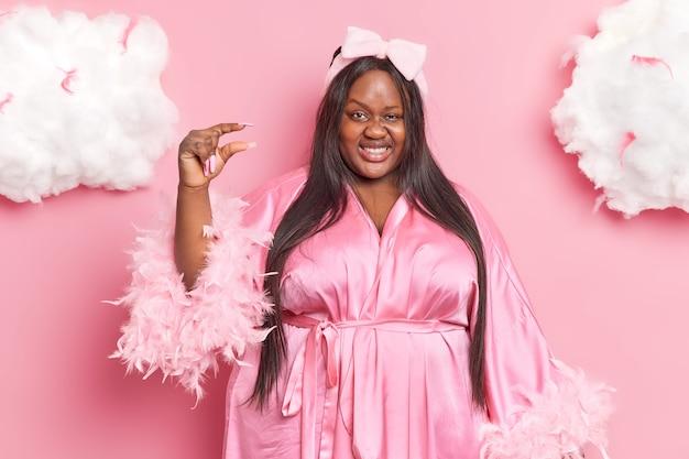 Une femme gaie de taille plus avec des formes de peau foncée, un objet minuscule ou petit montre des sourires de petite taille porte joyeusement une robe de chambre a une expression heureuse isolée sur le rose