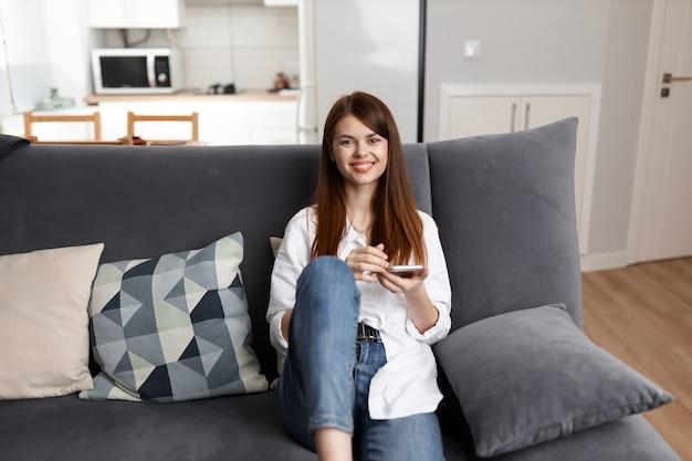 Femme gaie avec un téléphone dans ses mains est assise sur un canapé reste intérieur de l'appartement