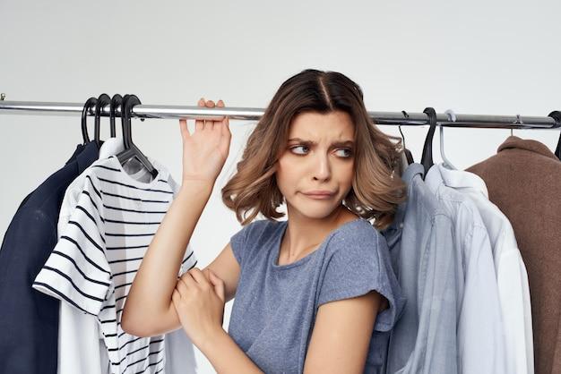 Femme gaie vêtements cintre commode mode intérieur fond isolé