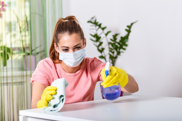 Femme avec un gant de protection et un masque facial saupoudrant de désinfectant et nettoyant la table. restez en sécurité.