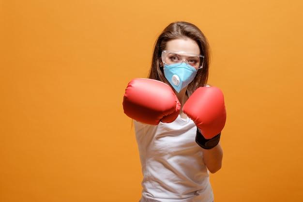 Femme en gants de boxe, mise en quarantaine à domicile, pandémie de coronavirus, bataille avec virus