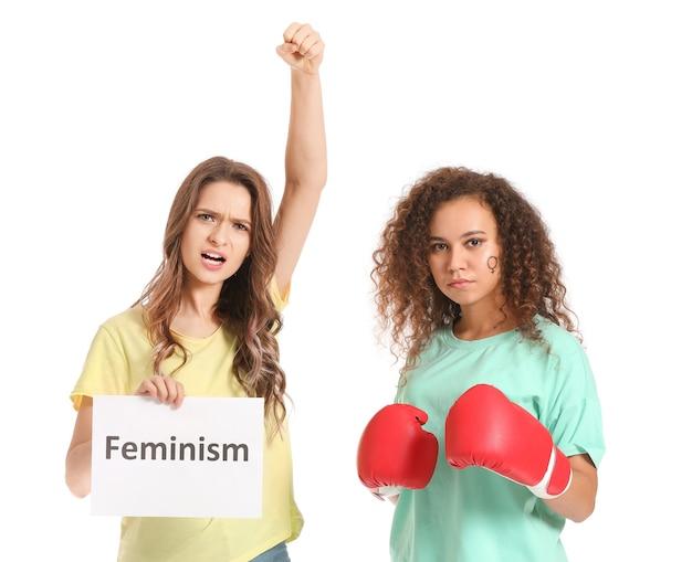 Femme en gants de boxe et son amie tenant du papier avec texte feminisme on white