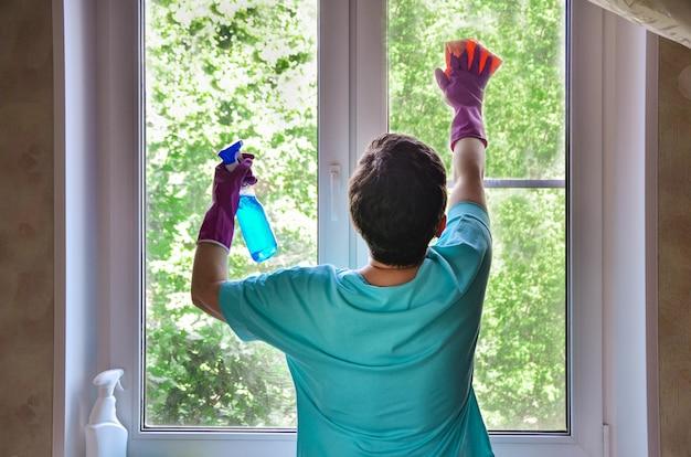 Une femme avec des gants en caoutchouc lave la fenêtre, tenant un spray nettoyant pour vitres dans les mains. services de nettoyage