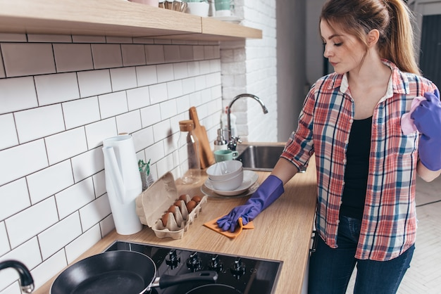 Femme en gants de caoutchouc, nettoyage de table de cuisine.