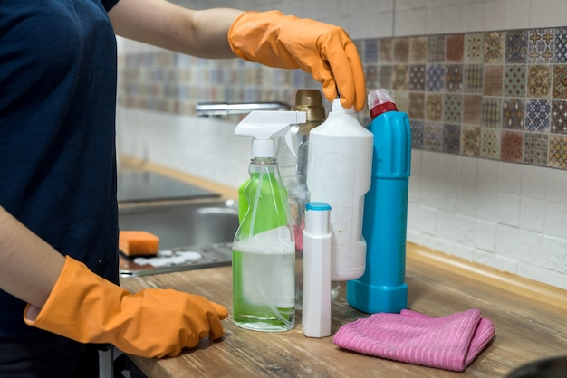 Femme en gants en caoutchouc tenant des bouteilles en plastique de liquide de lavage dans la cuisine