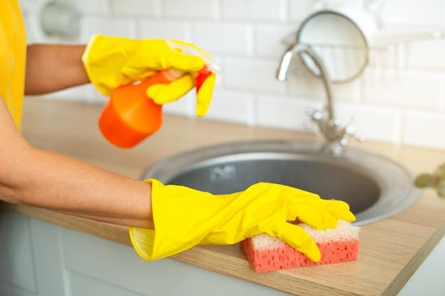 Femme en gants jaunes faisant le ménage avec un agent de nettoyage