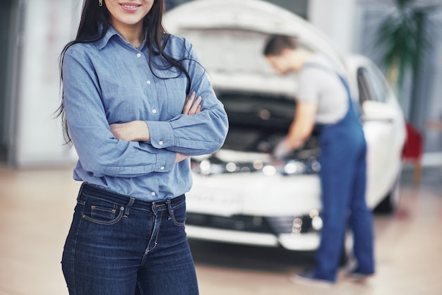 Femme, garage, voiture, obtenir, mécanique, service le mécanicien travaille sous le capot de la voiture