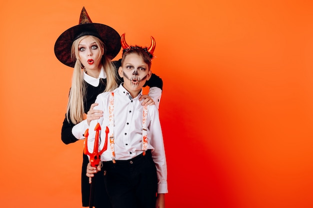 Femme et garçon dans le maquillage du diable se maquillant montrant l'émotion de merveille. halloween