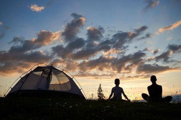 Femme et garçon près de camping au coucher du soleil