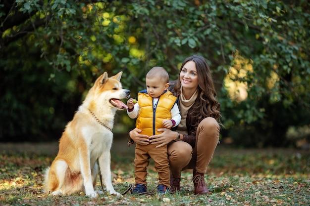Femme et garçon près du chien rouge au parc automne