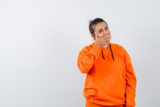 Femme gardant la main sur la bouche en sweat à capuche orange et à la gaieté